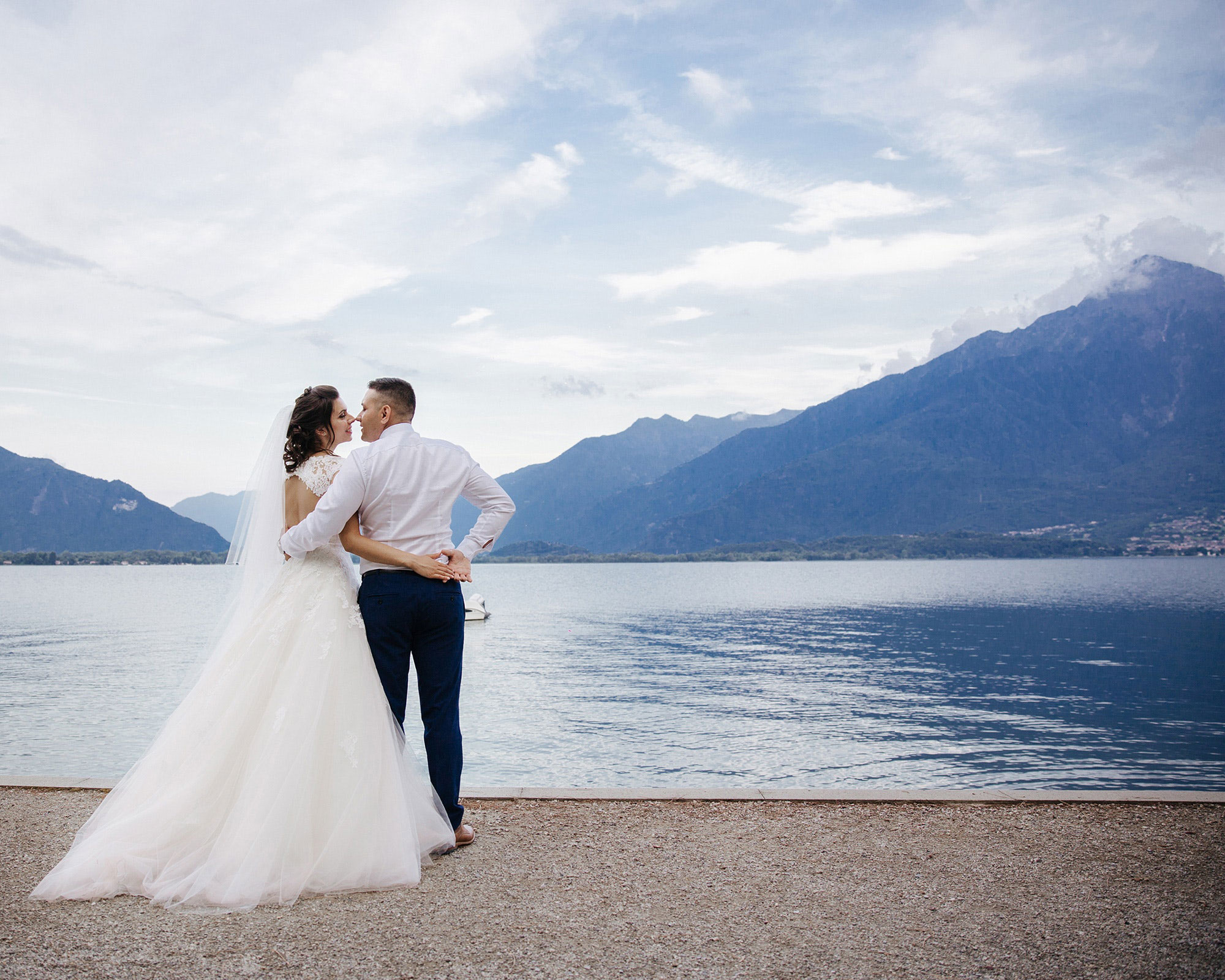 Bride and groom embracing by a lake
